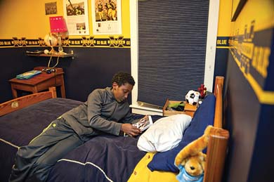 Feleke reads in his bedroom in the Logues' home. (Image: Leisa Thompson.)