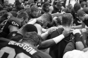 Harbaugh prays with team by David Turnley.