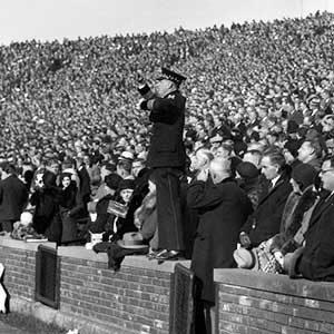 Nicholas Falcone conducting form atop the wall at Michigan Stadium