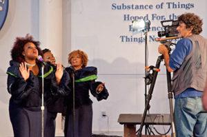Sacks on set with the Hallelujah Singers