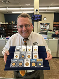 Patrick Heller displays a tray of gold coins from a display at Liberty Coin Service.
