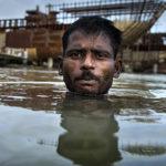 Environmental migrant Razek swims in the Buriganga River in Dhaka, Bangladesh.