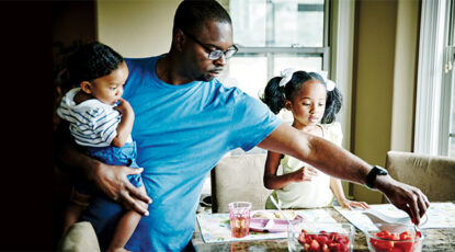 Father holding infant son while serving fresh fruit to daughter for breakfast