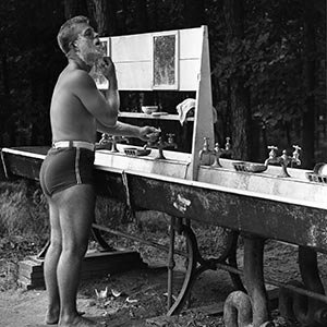 Camper shaves at outdoor sink.