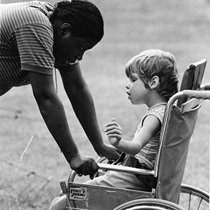 Boy in wheelchair with counselor.