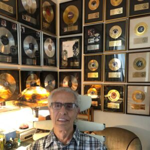 Perry in his office with gold and platinum records.