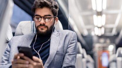 Young man reading an article on his phone and listening to podcasts while traveling by train.