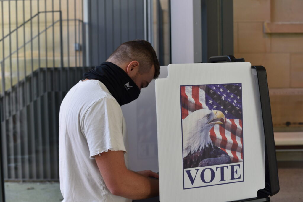 First-time voter Riley Freedman casts his vote at UMMA in October 2020.