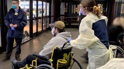 Nurse wheels patient to exit at U-M Hospital