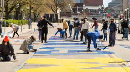 Students paint a mural in front of Rackham to celebrate 2021 graduates. (Image: Eric Bronson)