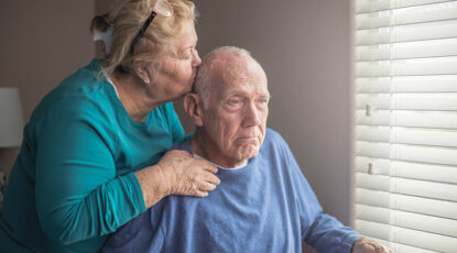 An elderly couple gazes out the window.