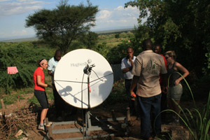 Recent U-M graduate Joan Ervin and Teddy Chenya adjust the satellite dish they helped to install to bring the Internet to rural Kenya.  (Photo: Job Mainye.)