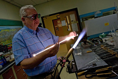 U-M scientific glassblower Harald Eberhart heats a tube of quartz to 2,000 degrees C. Eberhart, who has been blowing glass since age 14, can make complex, one-of-a-kind scientific instruments to order, saving the university time and money and creating new research possibilities for its scientists. (Photo: Martin Vloet, U-M Photo Services.)