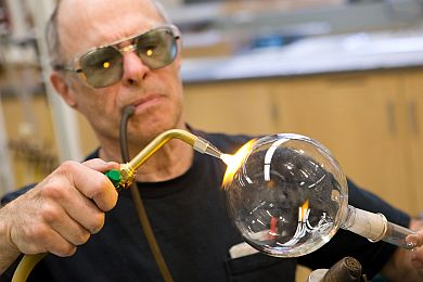 Roy Wentz uses a tube to blow air into an instrument he is repairing for the chemistry department. Wentz, 67, spent 10 years training his son the glassblowing trade, but many institutions have cut their in-house glassblowers, and the traditional knowledge is fading. (Photo: Martin Vloet, U-M Photo Services.)