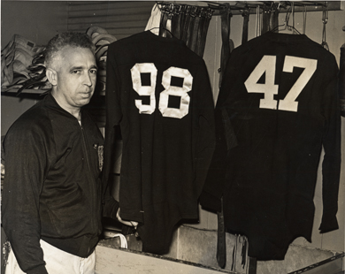 Henry Hatch, U-M's famed equipment manager, with two of the jerseys he retired: Tom Harmon (98) and Bennie Oosterbaan. (Photo courtesy U-M Bentley Historical Library.)