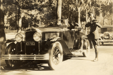 Police officer Chester Youngs alongside a car, circa 1920