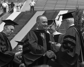 U-M President Harlan Hatcher confers an honorary degree to President Lyndon Baines Johnson during commencement 1964. (Image courtesy of U-M Bentley Historical Library.)