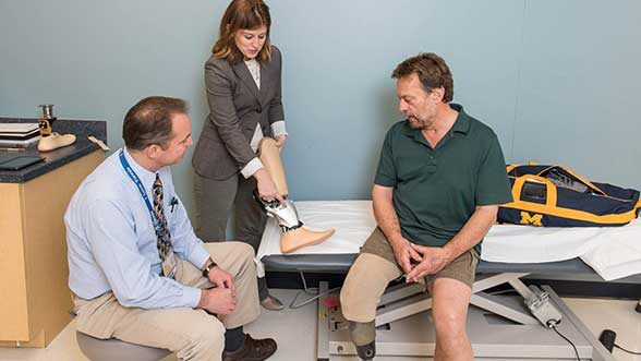 Jeffrey Wensman and Deanna Gates, assistant professor, Director of the Rehabilitation Biomechanics Laboratory at the University of Michigan help fit Roger Schulte (right) with a prosthesis. (Image: Scott C. Soderberg, Michigan Photography.)