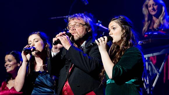 Davis singing in concert with his daughters
