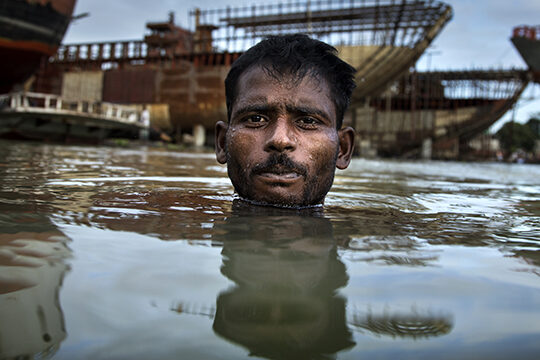 Environmental migrant Razek swims in the Buriganga River in Dhaka, Bangladesh.