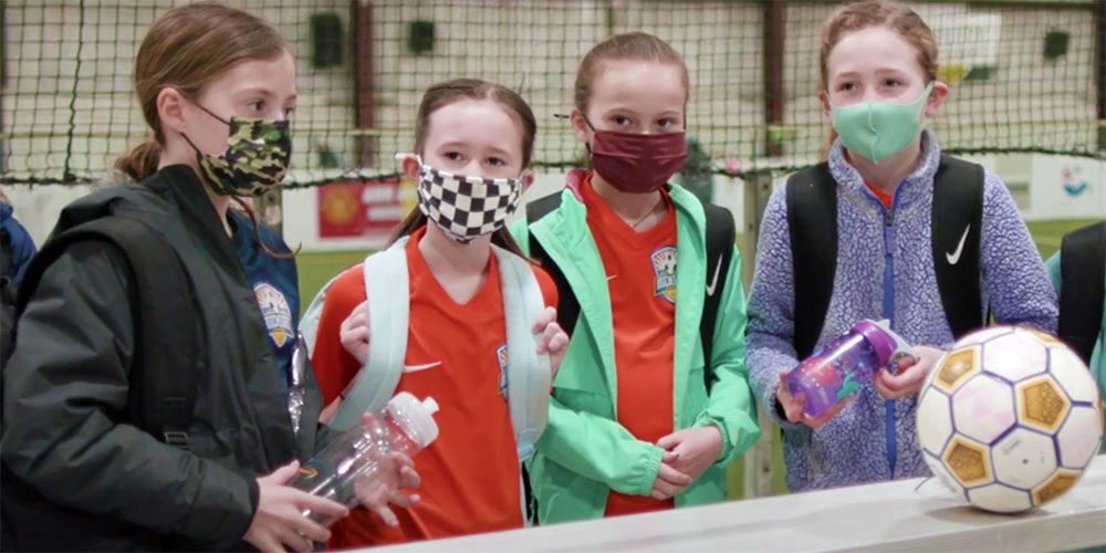 Girls in masks prepare to play soccer