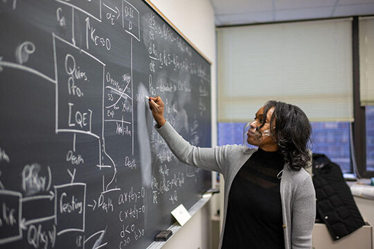 Woman writes complicated equation at blackboard