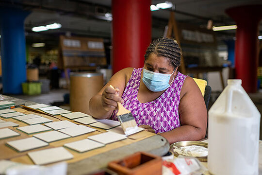 A woman makes coasters at Green Industries in Detroit