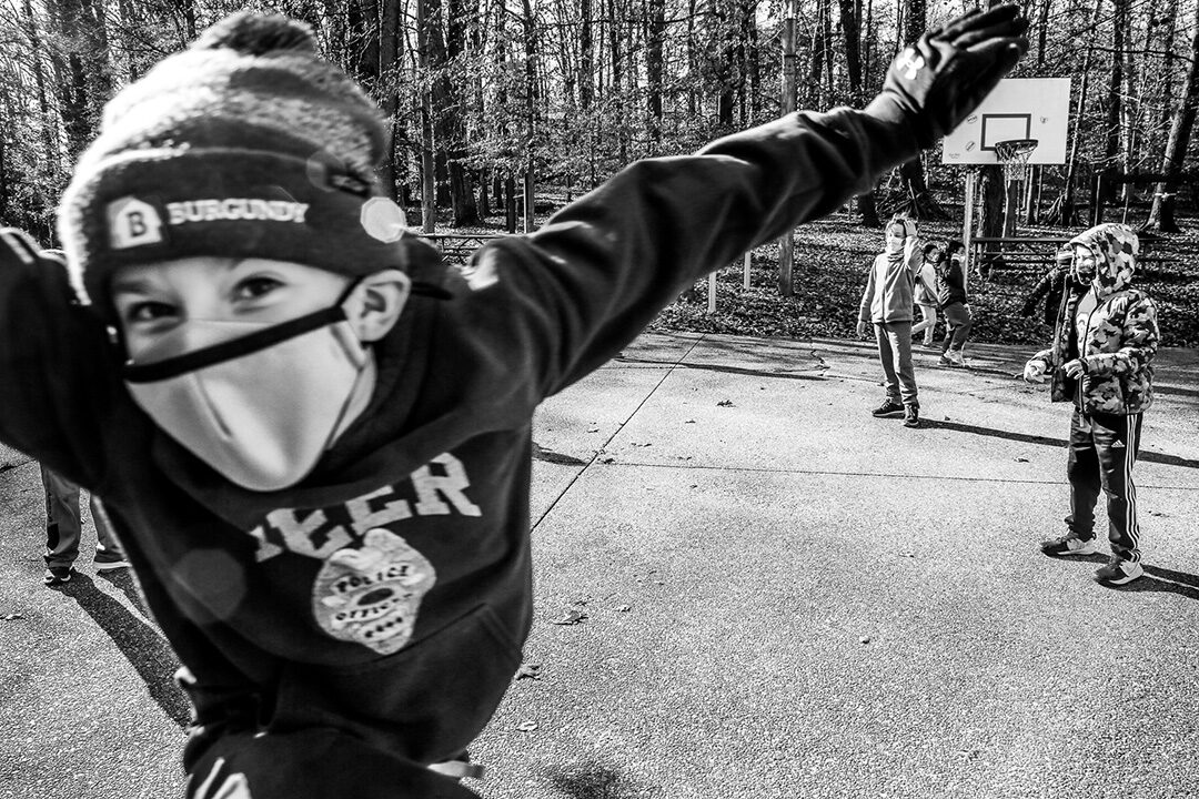 Photo bombing kid in a mask at play.